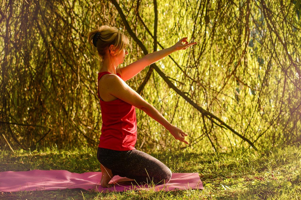 Femme à genou sur une couverture pratiquant une séance de relaxation