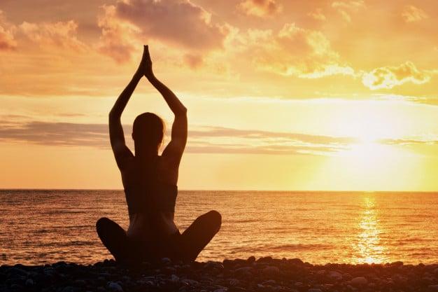 Posture de yoga devant un coucher de soleil